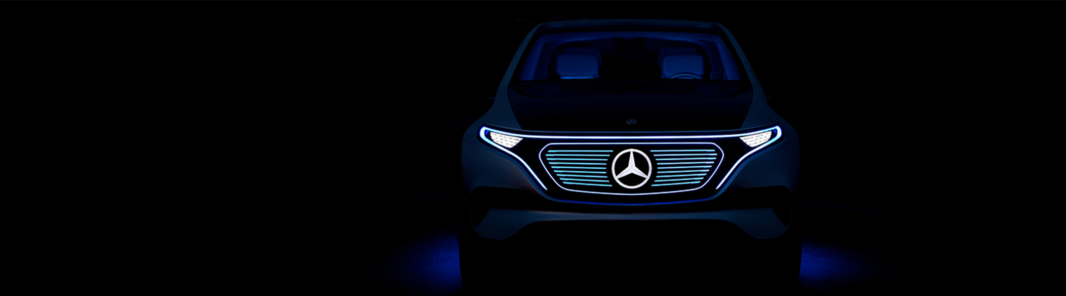 The front-end of a Mercedes-Benz Electric Intelligence concept car in the dark, with the grill, headlights and three-pointed star illuminated.