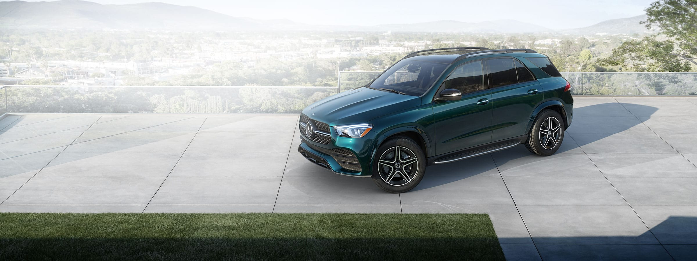 A dark green GLE SUV sits on a rooftop overlooking a lush landscape.
