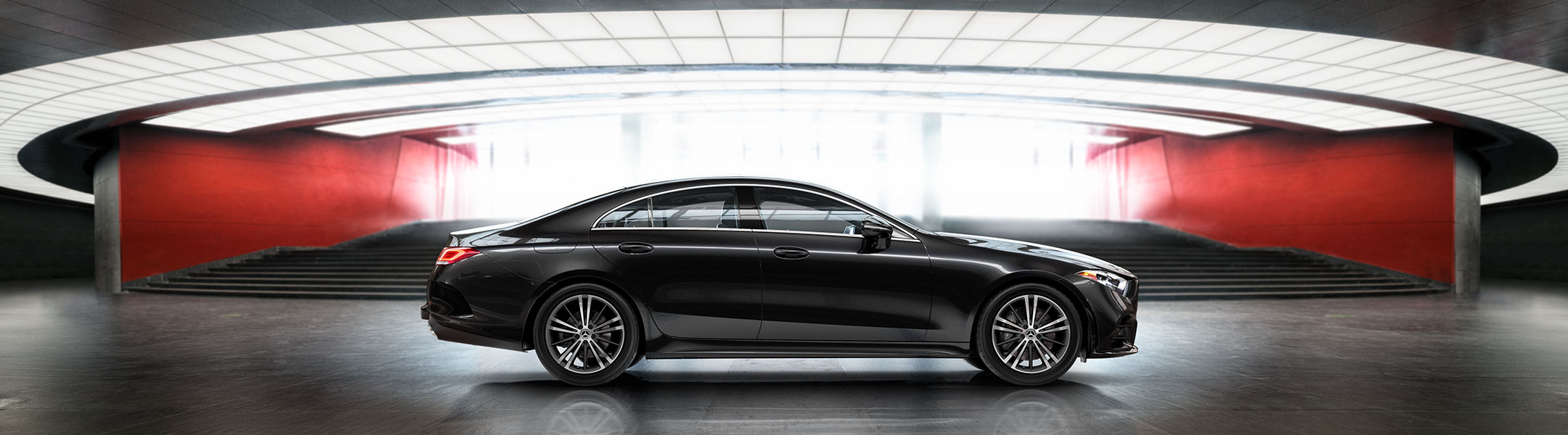 A black CLS is parked in front of a modern architectural background.