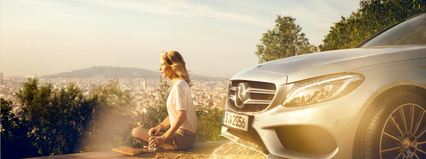 A woman sits on a ledge next to her silver Mercedes-Benz.