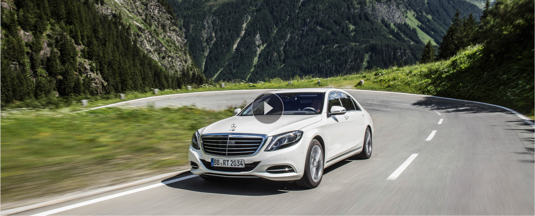 A white Mercedes-Benz driving on a curvy road among the mountains.