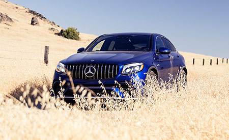 A blue Mercedes-Benz SUV drives through a field of wheat on a cloudless day.