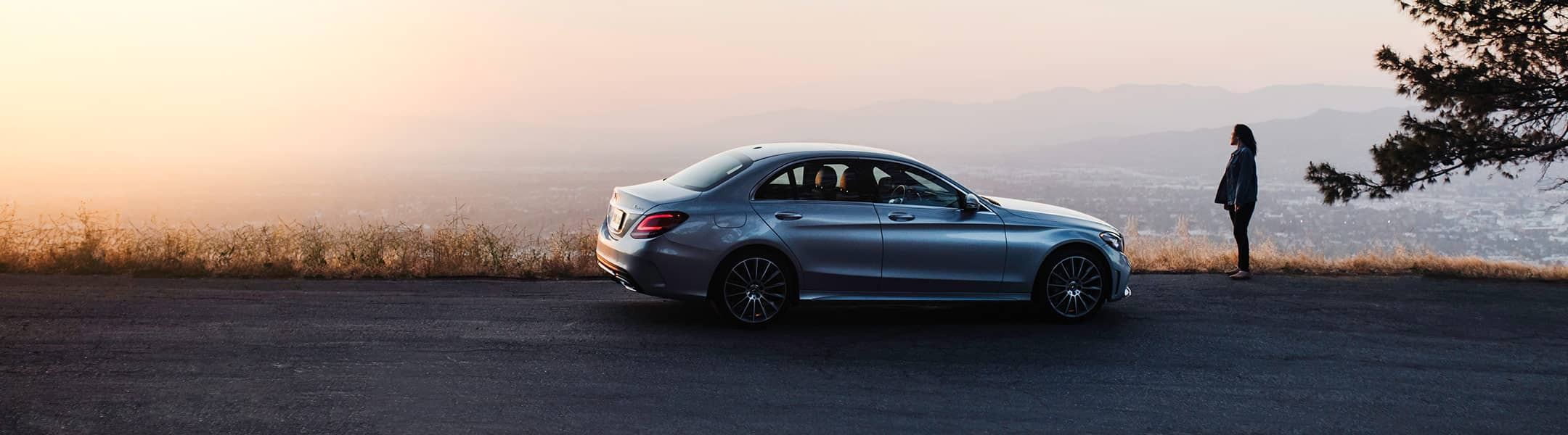 A person stands beside their Mercedes-Benz sedan at a scenic overlook.