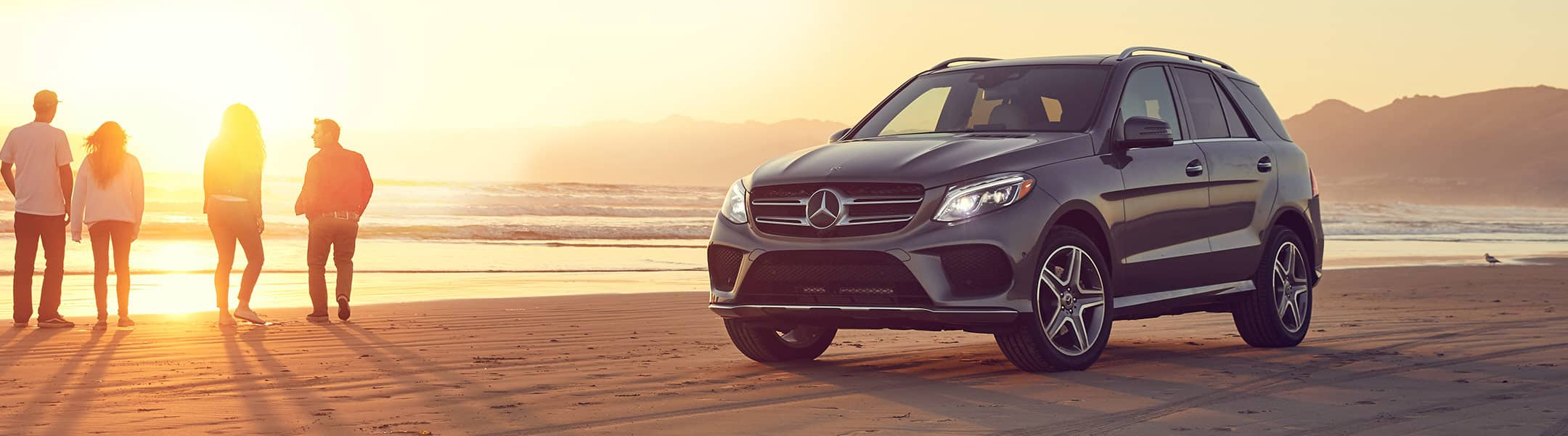 Four people watch the sunset as their Mercedes-Benz SUV is parked on a beach.