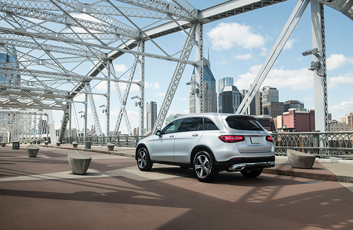 A silver Mercedes-Benz SUV drives across a bridge.
