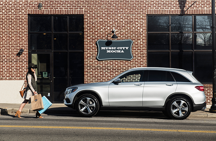 A silver Mercedes-Benz SUV is parked by a storefront.
