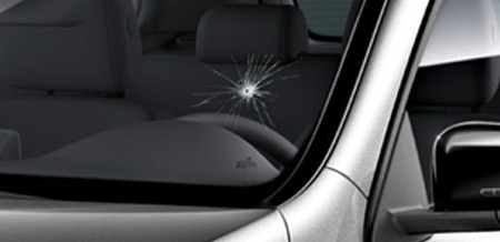 A close-up of a crack in the corner of a windshield.