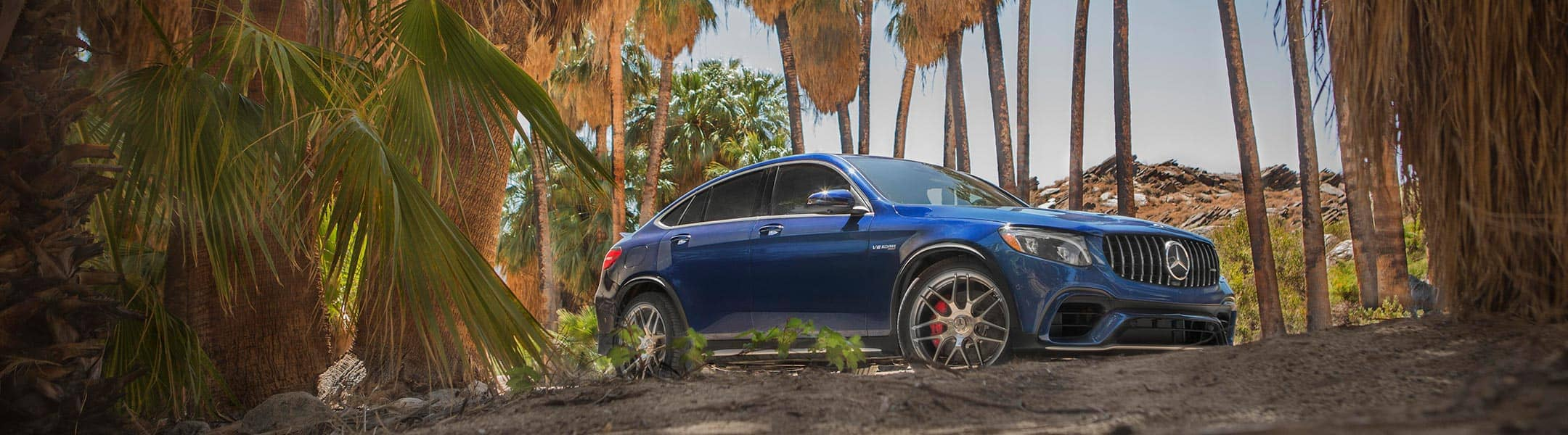 A blue Mercedes-Benz SUV drives through the backroads in a tropical setting.