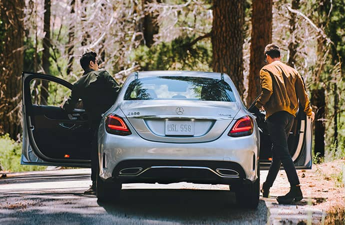 Two men get into a silver Mercedes-Benz parked on a backroad in the woods.
