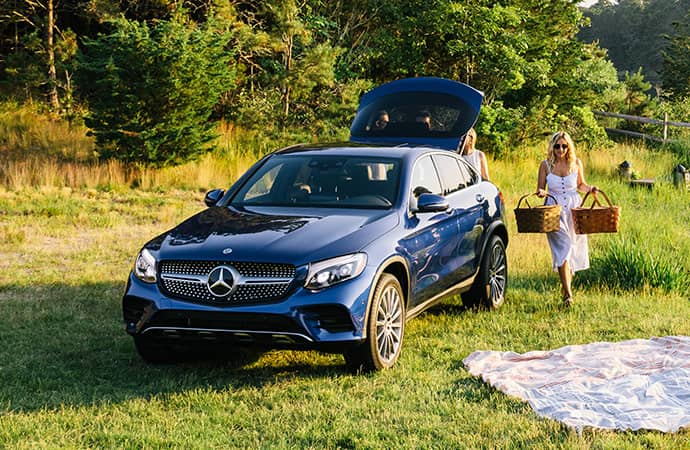 A woman unpacks for a picnic beside her blue GLE Coupe.