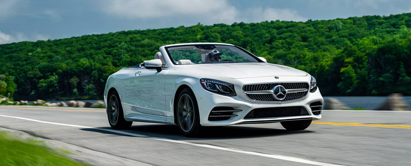 A White Mercedes Benz Cabriolet Breezes Along Main Road In The Afternoon