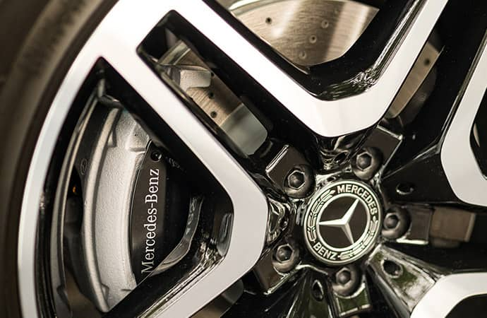 A close-up of the Mercedes-Benz logo at the center of a chrome rim.