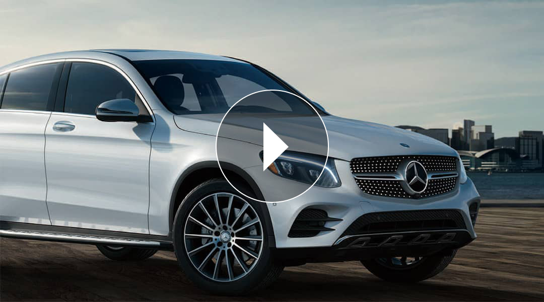 A white Mercedes-Benz GLE Coupe is parked, headlights glistening.