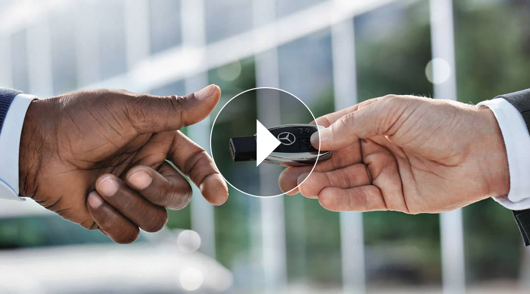 A Mercedes-Benz key fob is being handed from one person to another.