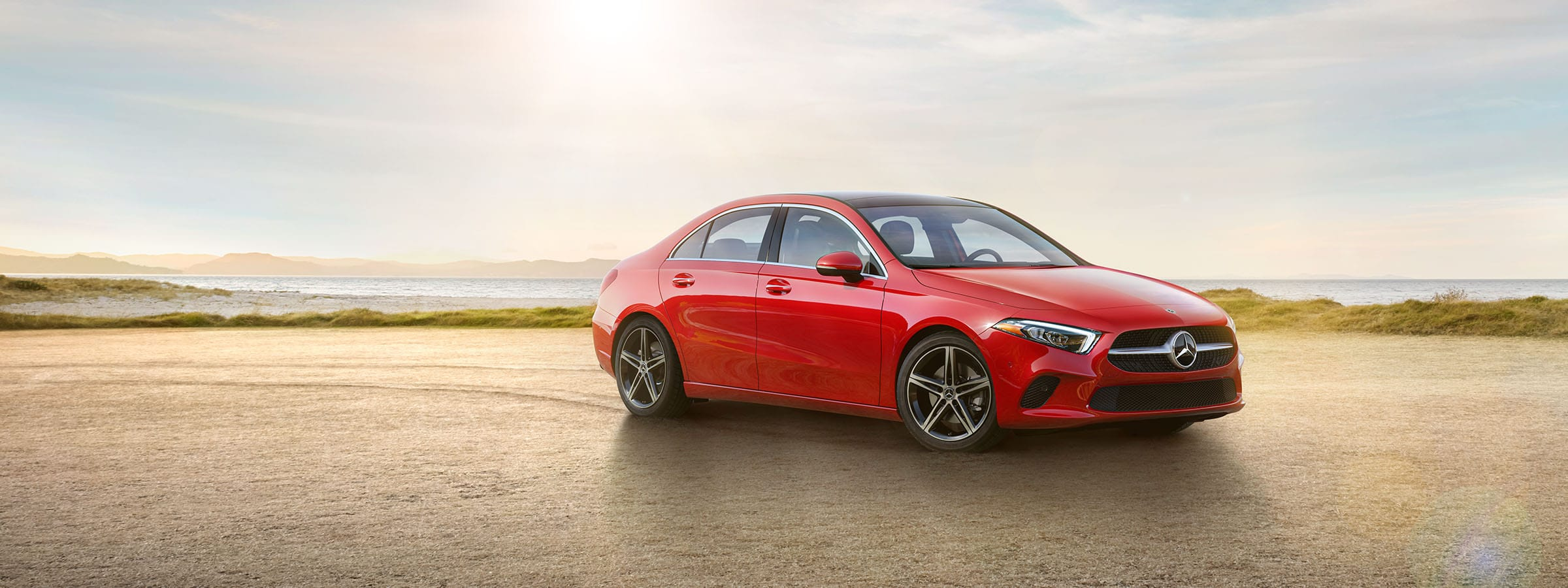 The 2019 A-Class Sedan in Jupiter Red with LED Lights parked on a beach.