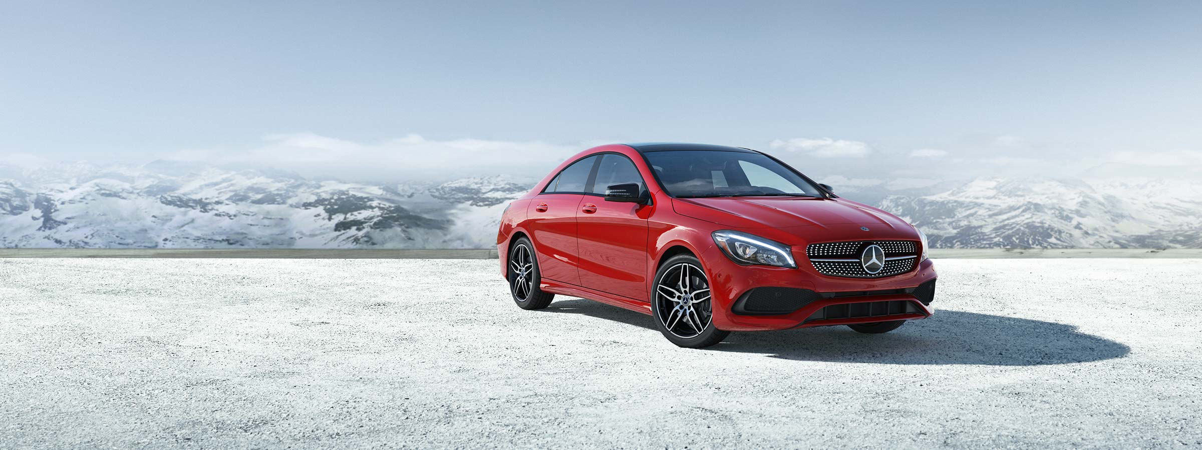 A Red 2019 Cla 250 Coupe Parked In Front Of Snow Covered Mountains