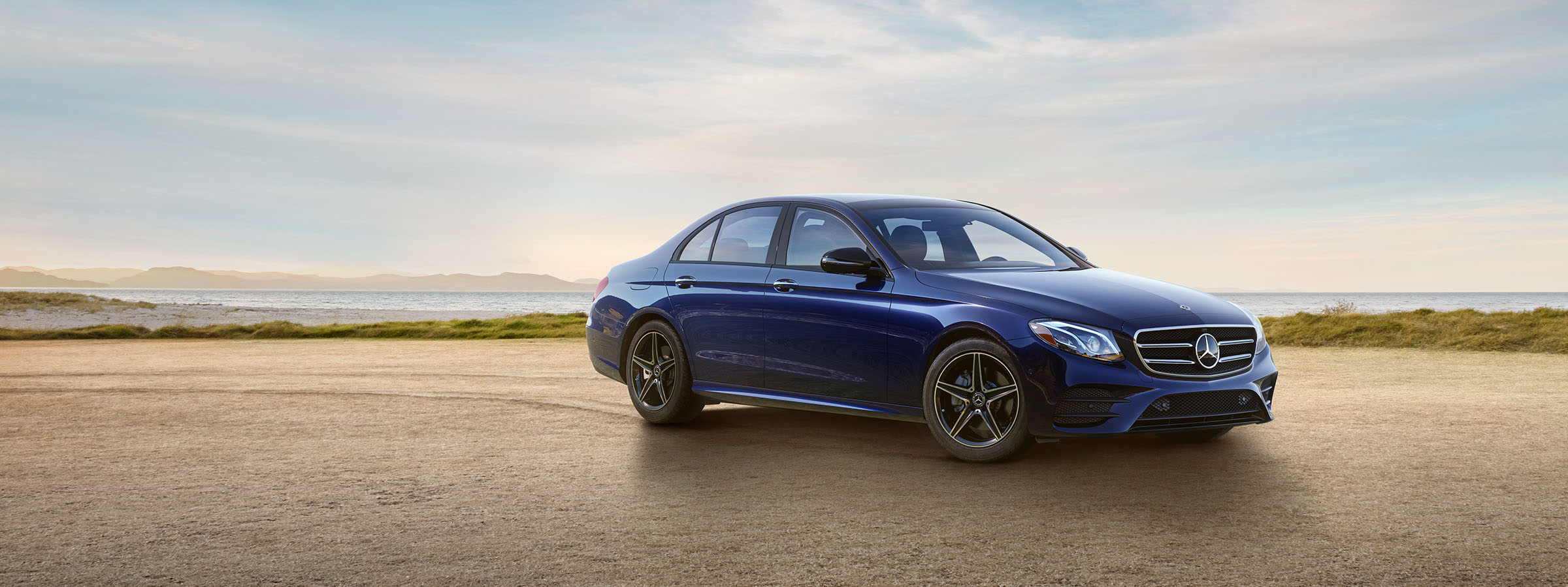 The 2019 E-Class Sedan in Lunar Blue with LED Lights and AMG Line Exterior with Night Package parked on a beach.