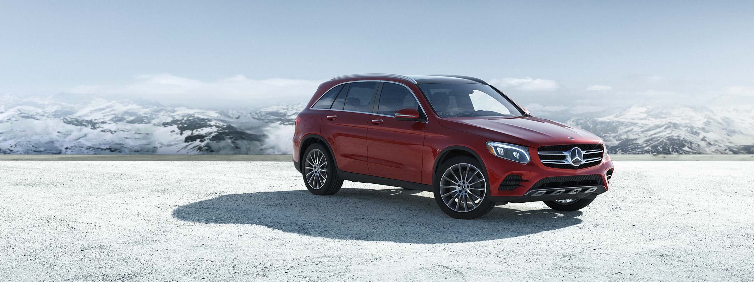 A red 2019 GLC 300 SUV parked in front of snow-covered mountains.