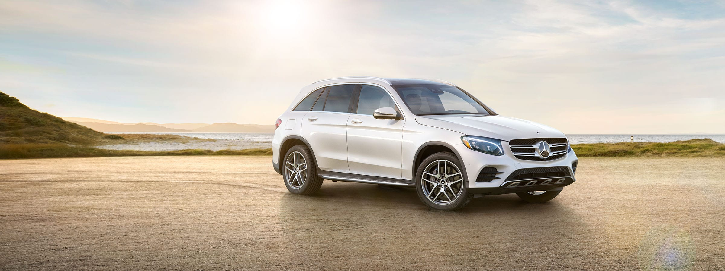 The 2019 GLC SUV in designo Diamond White with AMG Lining and Exterior Lighting Package parked on a beach.