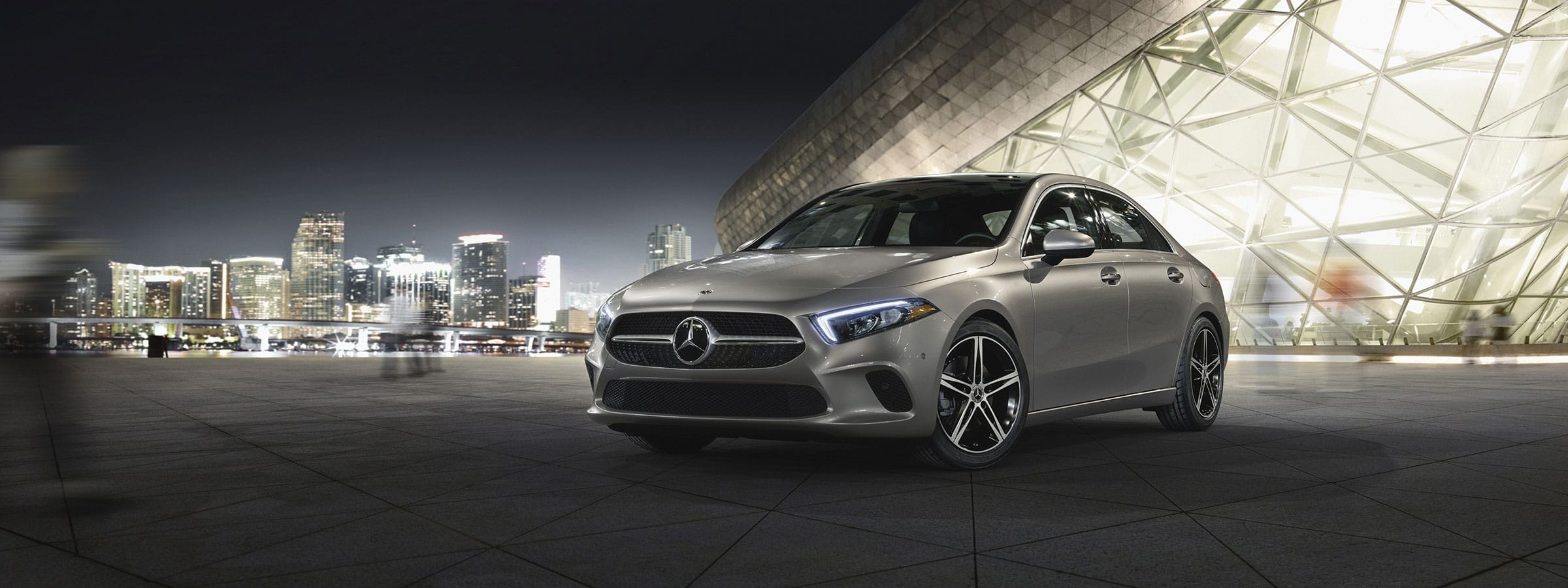 The 2021 A-Class Sedan in Iridium Silver with AMG Line Exterior and LED lights parked in the snow.