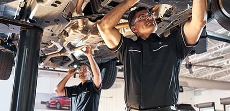Two service technicians work on the underside of a lifted vehicle.
