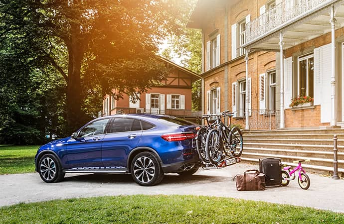 A blue SUV is parked in front of a house with multiple bikes on the bike rack and luggage nearby.