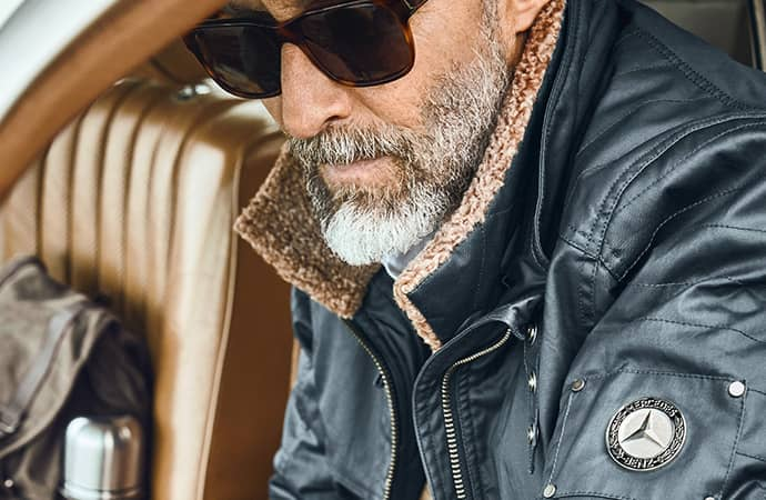 A bearded man is wearing a Mercedes-Benz branded leather jacket.