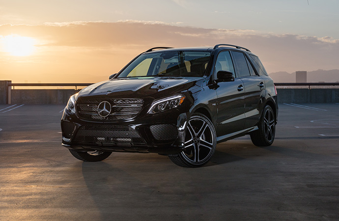 A black Mercedes-Benz SUV is parked on a garage rooftop as the sun goes down