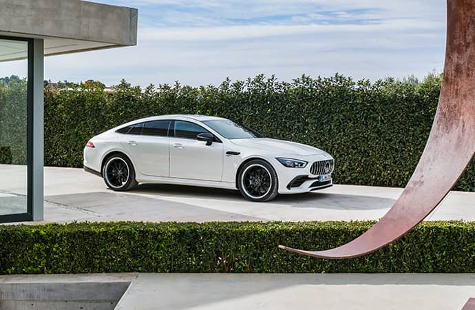 A white Mercedes-AMG GT 4-Door Coupe sits in the driveway of a modern home.