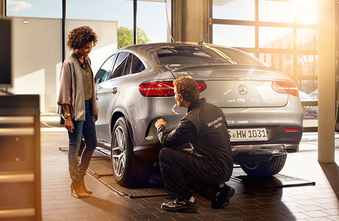 A woman speaks to a Mercedes-Benz Service Technician as he works on her vehicle.