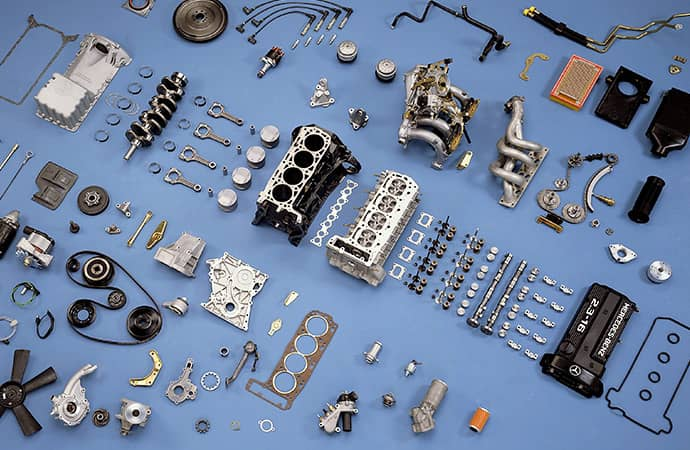 Engine parts, disassembled and laid out on a flat surface.
