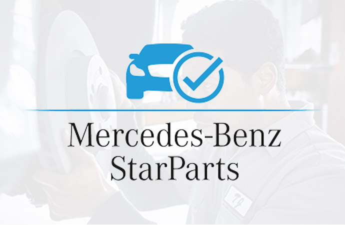 A person with a towel wipes down the top of an engine near the Mercedes-Benz logo.