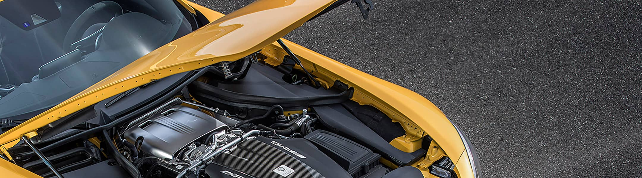 A view under the hood of a yellow Mercedes-AMG GT.