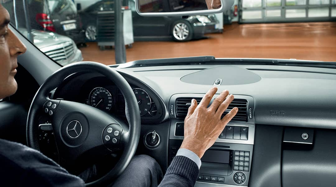 An interior image of a Mercedes-Benz with a person's hand over the air vents.