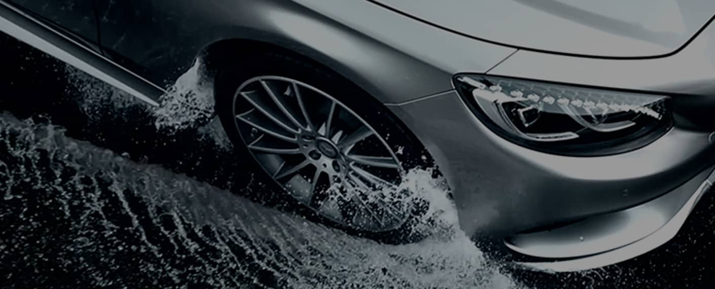 A silver Mercedes drives through a few inches of water.