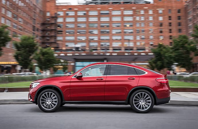 A profile view of a red Mercedes-Benz SUV as it drives in front of a large building.