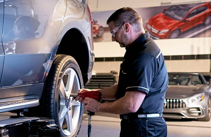 A Mercedes-Benz service technician works on the rear wheel of a vehicle.