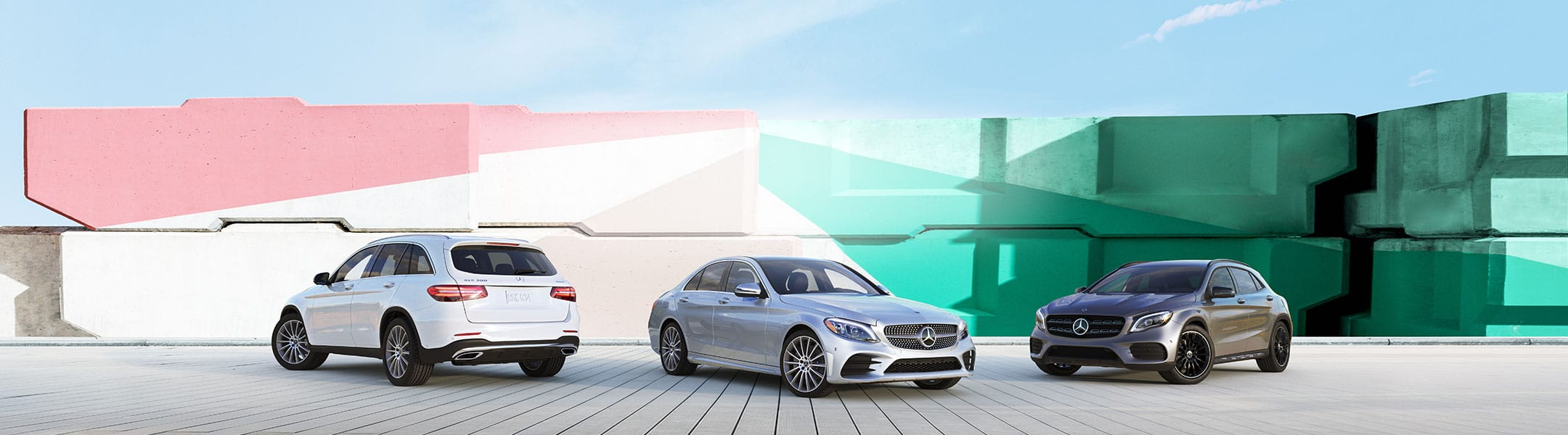 Three new Mercedes-Benz vehicles sit parked in front of a bright, multi-colored mural.